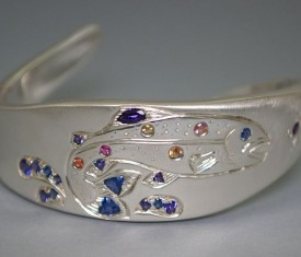 Custom rainbow trout cuff featuring many of client's own Yogo sapphires with Montana sapphire accents.