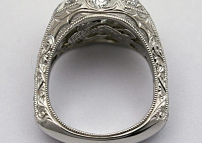 The whole side of the ring is decoratively hand engraved on this platinum diamond engagement ring.