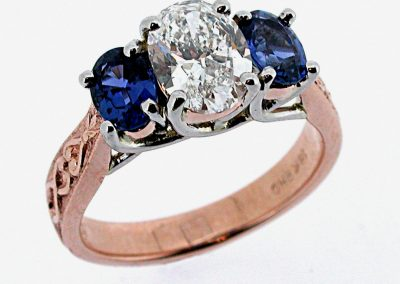 2ct oval diamond engagement ring with 1.5ct total weight Yogo sapphire accent side stones, platinum and rose gold